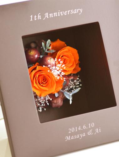 アンティーク風のブラウンフレームに鮮やかなオレンジ色が映えるプリザーブドフラワーアレンジメント